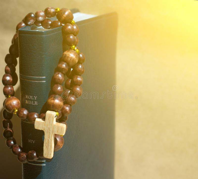spiritual background with Wooden rosary on the Bible in the aureole of the divine of Divine Rays and place for inscription royalty free stock images