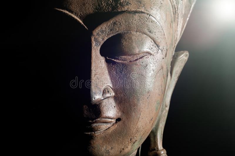 Spiritual enlightenment. Buddha head with divine light. Bronze s royalty free stock images