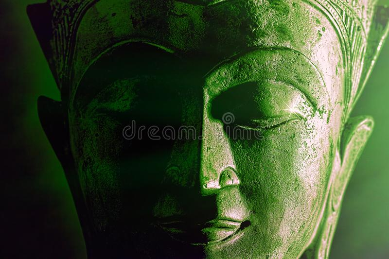 Spiritual enlightenment. Green buddha face statue close-up. Bold graphic image. With atmospheric green tone light and star highlight. Religious alternative stock images