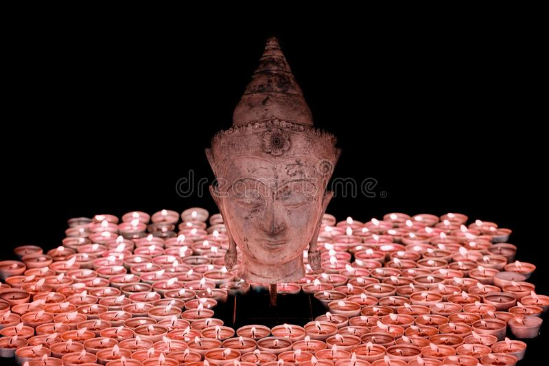Spiritual enlightenment. Traditional buddha head statue illuminated by candles. Meditation, mindfulness and spirituality royalty free stock image