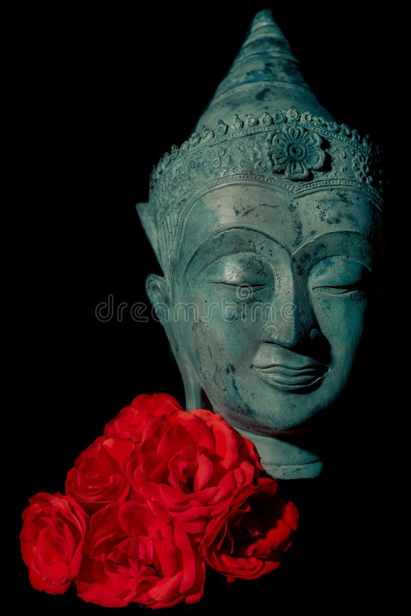 Spiritual love. Beautiful blue buddha head statue with red roses stock photography
