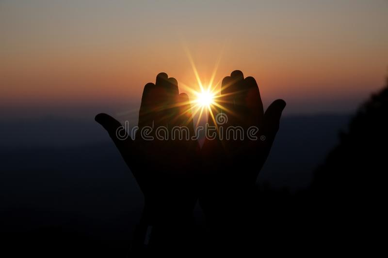 Spiritual prayer hands over sun shine with blurred beautiful sunset background. Faith of christian concept: Spiritual prayer hands over sun shine with blurred stock image