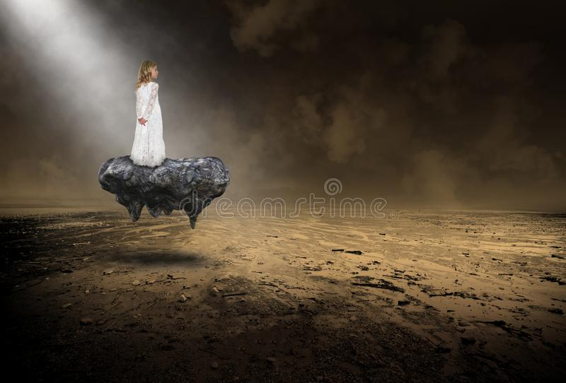 Spiritual Rebirth, Peace, Hope, Love. Surreal scene of a young girl in a desolate desert floating on a rock. Abstract concept for peace, hope, love, nature, and royalty free stock images