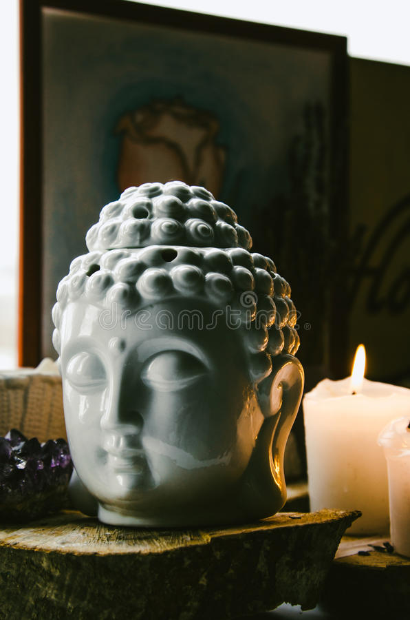 Spiritual ritual meditation face of Buddha ametist candles on old wooden background. Spiritual ritual meditating face of Buddha ametist candles on old wooden stock image