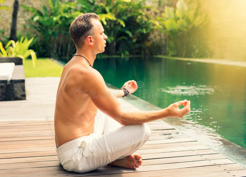 Spiritual man meditating in morning. Spiritual young man meditating in morning by the tropical pool stock images