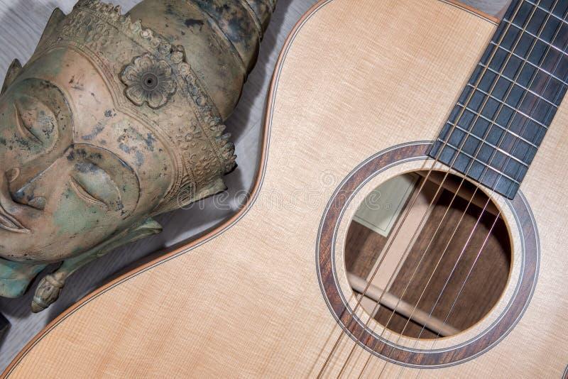 Spirituell musik Buddha som mediterar med folklig akustisk gitarr arkivfoto