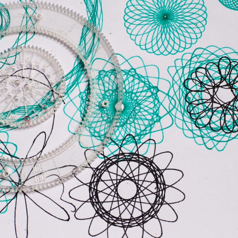 Spirograph retro toy. With symtrical flower ornaments on a paper royalty free stock photos