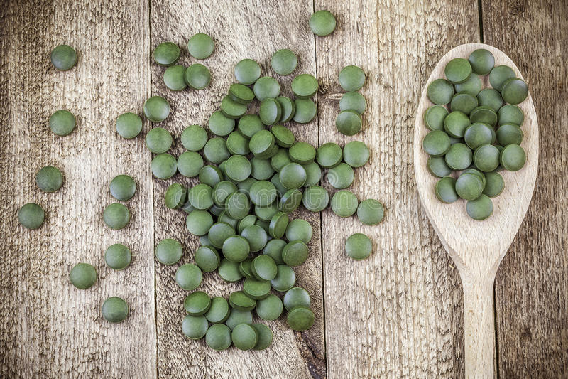 Spirulina,小球藻在木匙子的补充药片在桌上 免版税库存图片