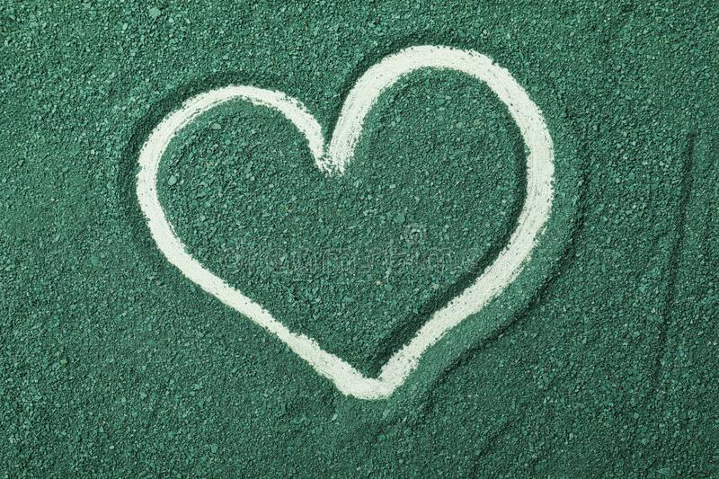 Spirulina algae powder with drawn heart shape as background. Top view royalty free stock photos