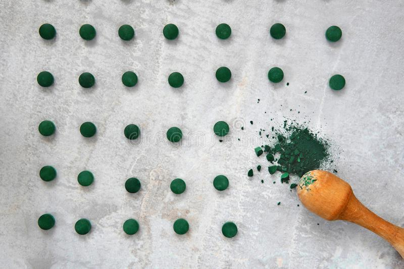 Spirulina algae powder and tablets on gray background from top view royalty free stock images