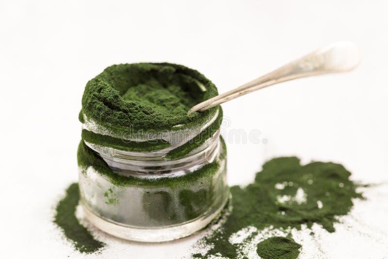 Spirulina-Grünpulver im Glasgefäß mit Löffelsatz auf einem strukturierten Hintergrund lizenzfreies stockbild