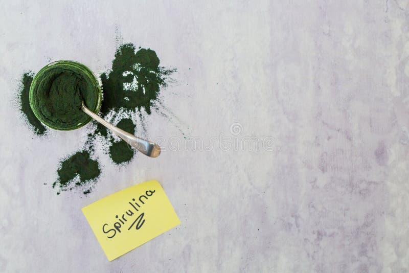 Spirulina green powder on single spoon with word spirulina as a sticky note. Spirulina health powder, green powder, health supplement on a single spoon, textured stock photo