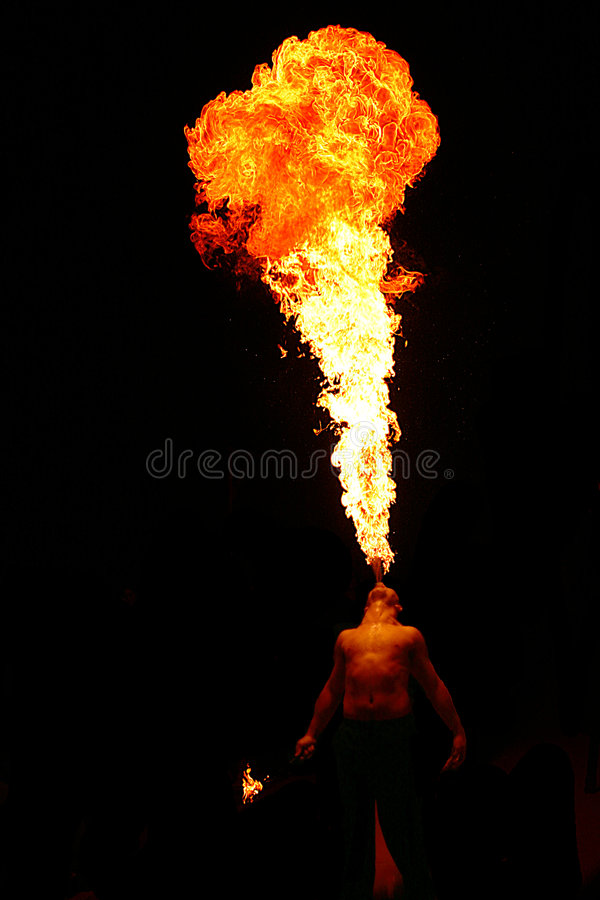 Spit fire. Some man spiting fire in a party stock image