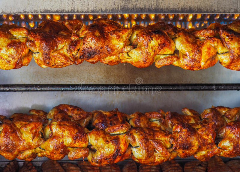 Spit-roasted rotisserie chickens under gas flame stock photography