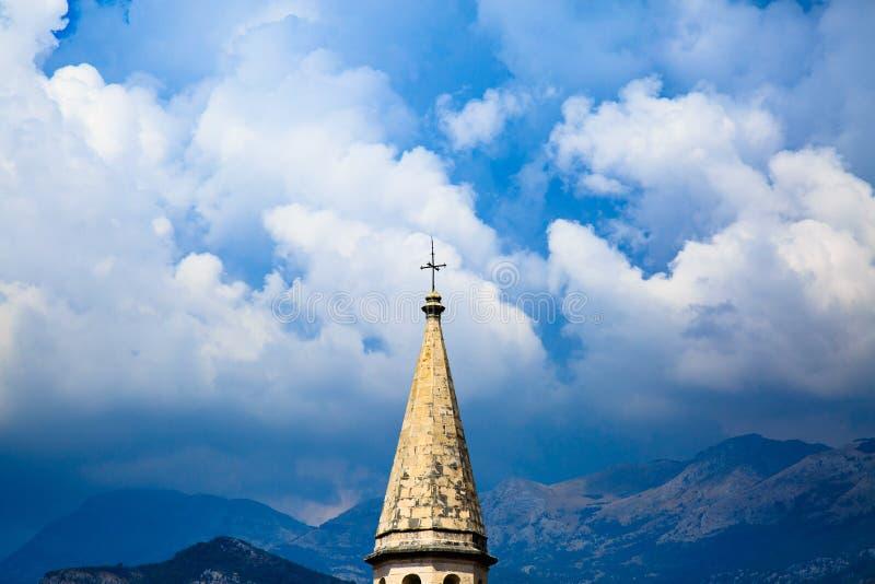 Spits van middeleeuwse katholieke kathedraal op achtergrond van stormachtige hemel, dramatische wolken en bergketens Heilige Ivan stock fotografie