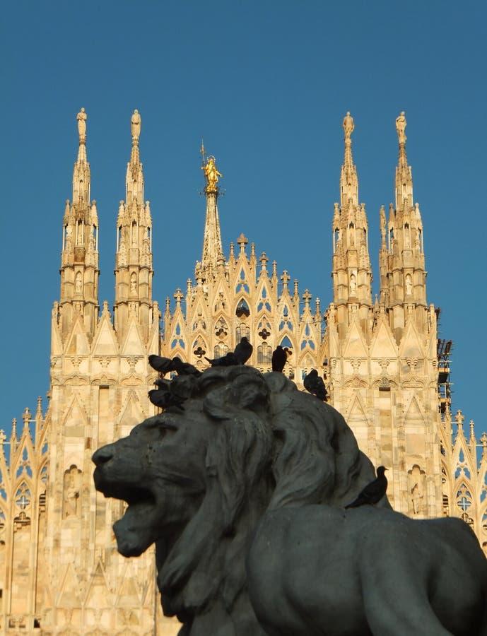 Spitsen van de Duomo-Kathedraal in Milaan met een leeuw in de voorgrond, die deel van het standbeeld van Victor Emmanuel II uitma stock foto