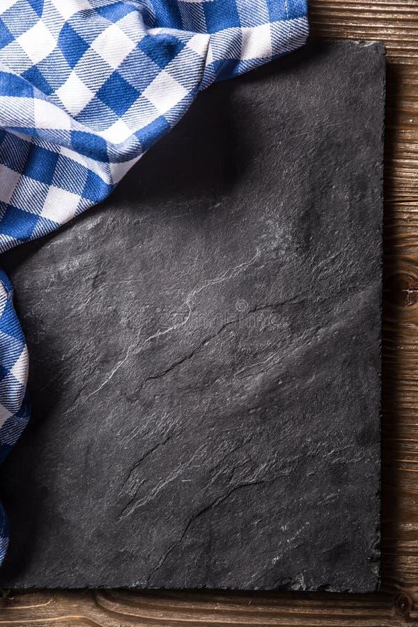 Spitze der blauen karierten Tischdecke der Ansicht auf schwarzem Schieferbrett stockfoto
