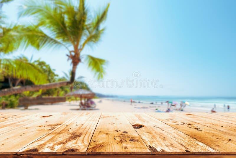 Spitze der hölzernen Tabelle mit Meerblick, Palme, ruhigem See und Himmel am tropischen Strandhintergrund lizenzfreies stockfoto