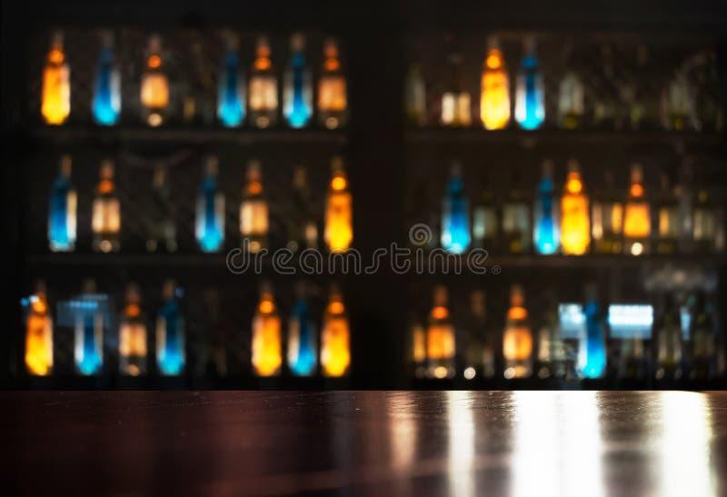 Spitze der hölzernen Tabelle mit orange NeonBlaulicht der Alkoholflasche im dunklen Bar- und Vereinhintergrund stockfotos