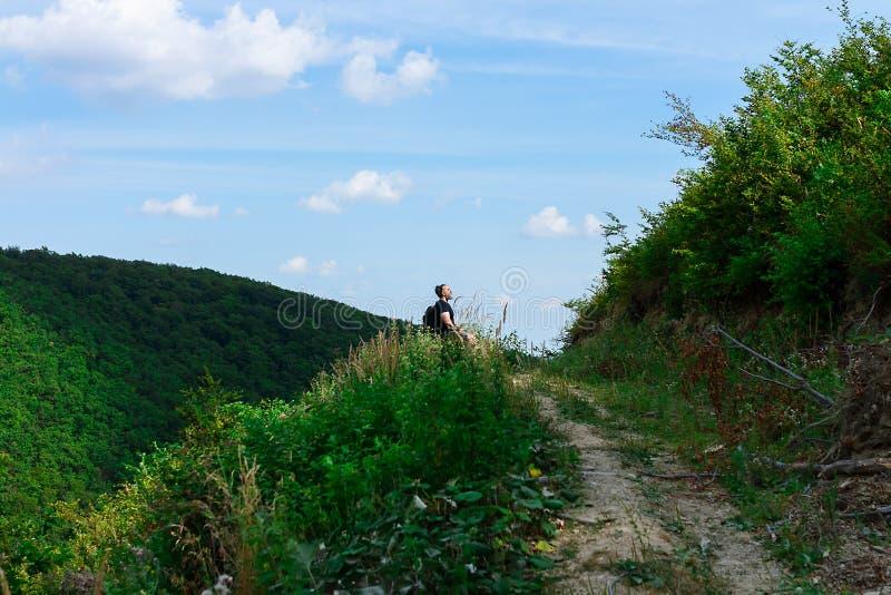 Spitze des Hügels, der Spur, die zu die Spitze führen und einer einsamen sitzenden und entspannenden Männerfigur lizenzfreie stockbilder
