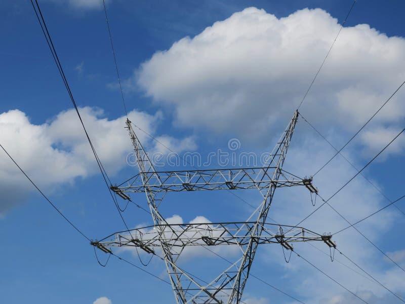 Spitze eines Hochspannungsturms mit Linien gegen te blauen Himmel lizenzfreie stockfotos