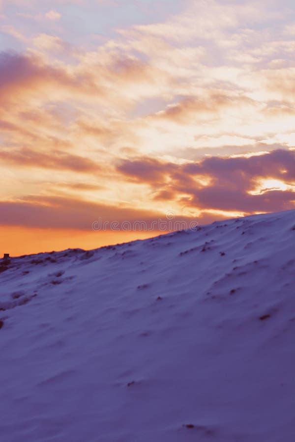 Spitze eines schneebedeckten Berges an einem Wintertag mit schönem Sonnenunterganghimmel im Hintergrund lizenzfreie stockbilder