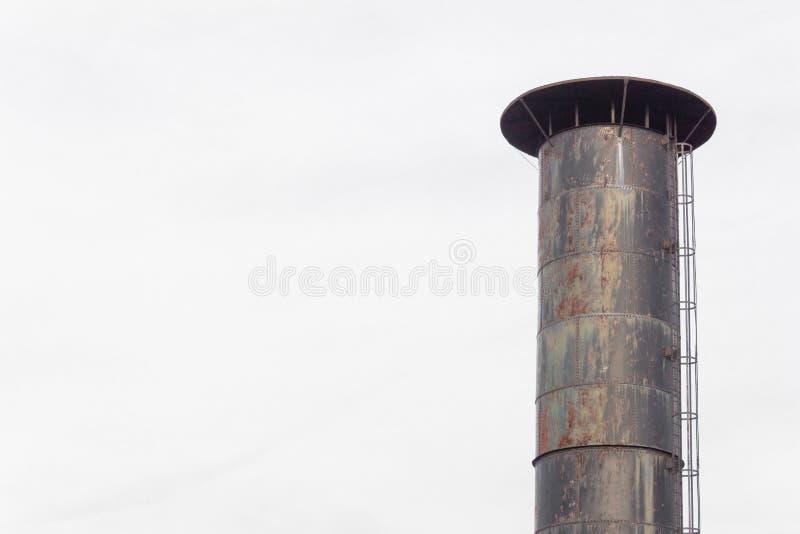 Spitze eines Schornsteins mit der angebrachten eingesperrten Außenleiter lokalisiert gegen einen grauen Himmel, Kopienraum stockbild