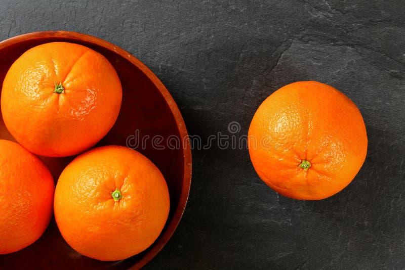 Spitze hinunter Ansicht, ganze Orangen in hölzerner Schüssel, eine nahe bei ihr auf schwarzem Steinbrett stockfoto