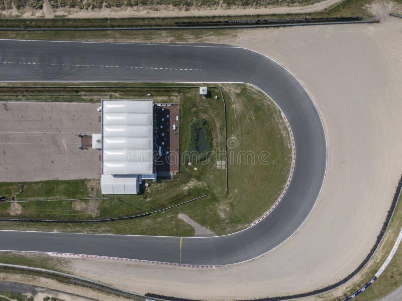 Spitze hinunter Vogelperspektive der Kurve im Motorsportrennstreckestromkreis mit Sandstraßenrand stockbilder