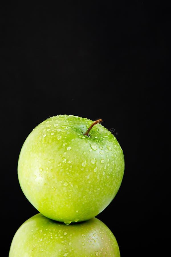 Spitze von grünem nassem frischem Apple auf schwarzem Hintergrund lizenzfreie stockfotografie