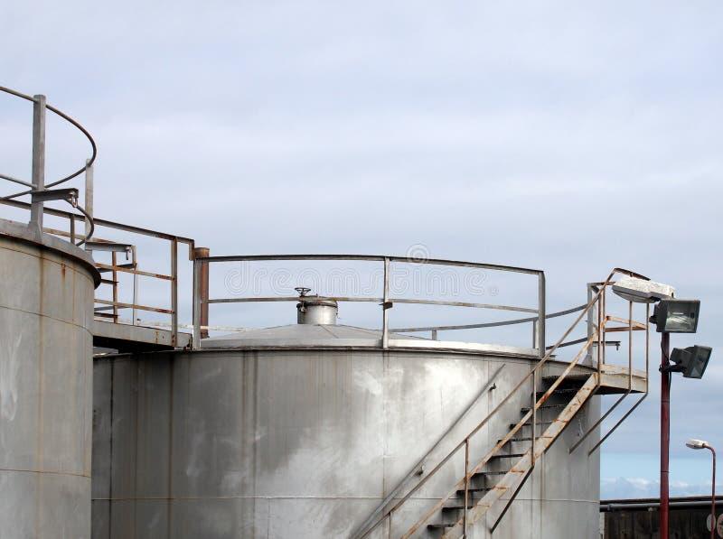 Spitze von großen alten silbernen industriellen Stahlsammelbehältern mit verrostender Treppe und Gehweg der Regelventile gegen ei stockbilder