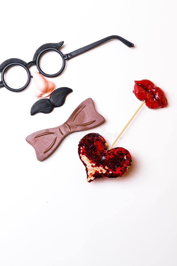 Spitzen- oder flache gelegte Ansicht von Passfotoautomatstützen ein Schnurrbart, Gläser, rote eine Herzform und eine Fliege auf f stockbild
