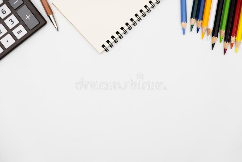 Spitzenansichtnotizbuch mit Farbbleistift auf weißer Tabelle lizenzfreie stockbilder