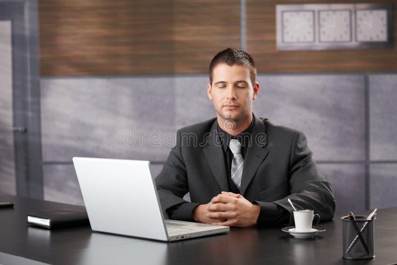 Spitzenmanager, der im eleganten Büro meditiert stockfotos
