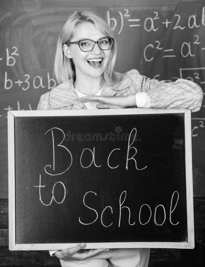 Spitzenweisen, Studenten zurück zu Schule zu begrüßen Lehrerfrauengriff-Tafelaufschrift zurück zu Schule Es ist Schulzeit stockfoto