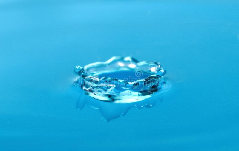 Splash of blue water with drop stock image