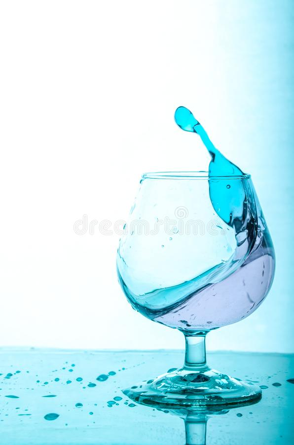 Splash of blue water in a glass. White Background. Splash of blue water in a glass. White Blue Background royalty free stock photos