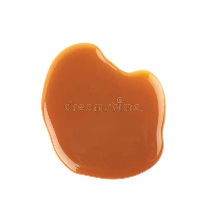 Splash of caramel sauce isolated. Over the white background royalty free stock photo