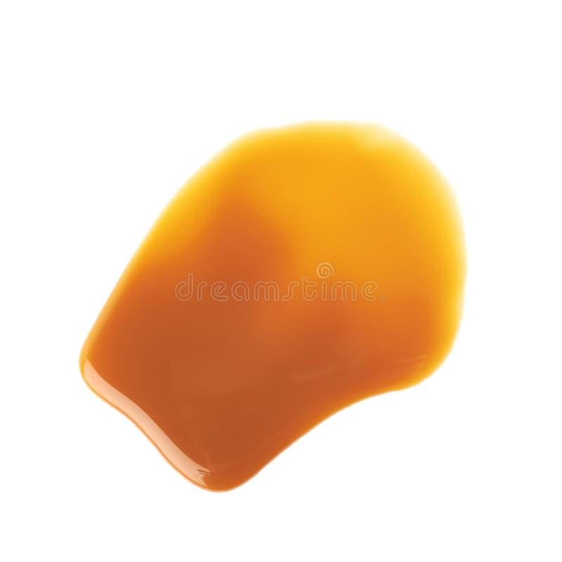 Splash of caramel sauce isolated. Over the white background royalty free stock image