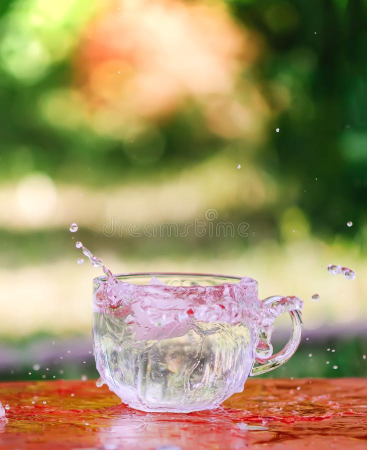 Splash of cool fresh water with ice cube in transparent glass cup in the table outoors in summer day. royalty free stock photo