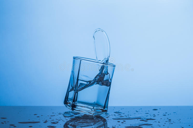 Splash in a glass of water on a blue background.  stock photo