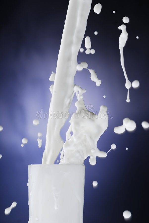Splash of Milk. Milk splashing while being poured in a glass stock photography