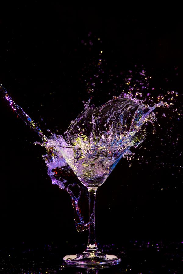 Splash Photography. Burst of Colorful Liquid in Wine Glass. Isolated Over Black Background stock image