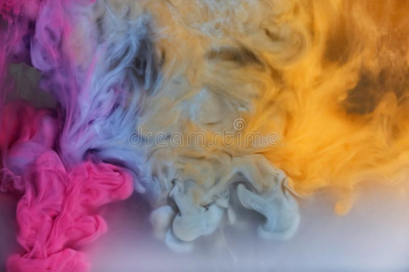 Splash of pink, light blue and yellow inks royalty free stock photo