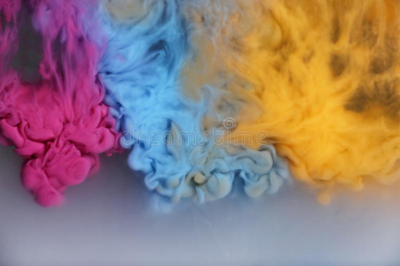 Splash of pink, light blue and yellow inks stock photo