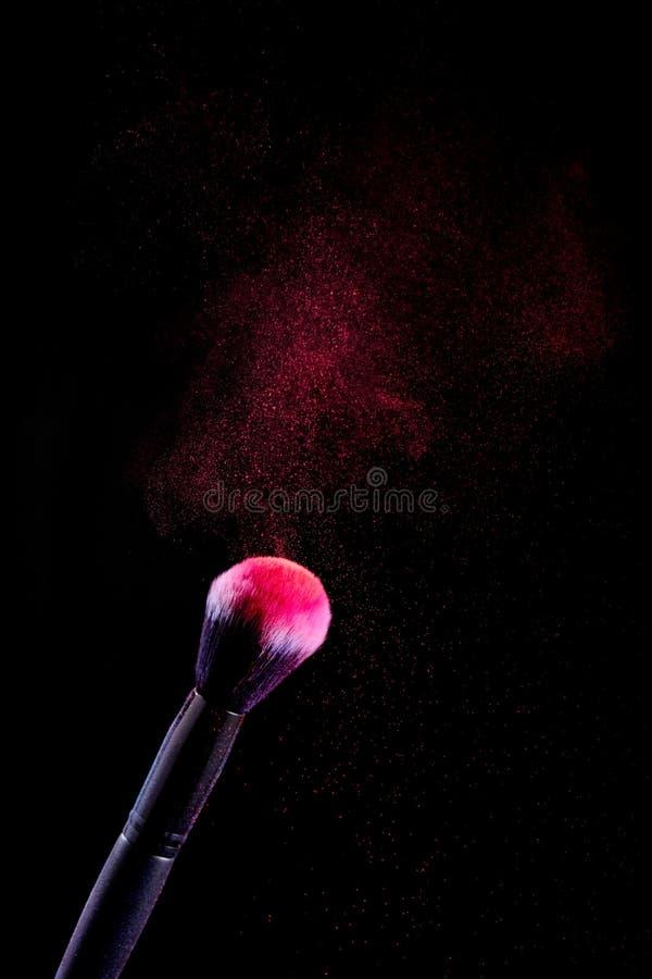 Splash of powder on a black background brushes for make up on a black background royalty free stock photo