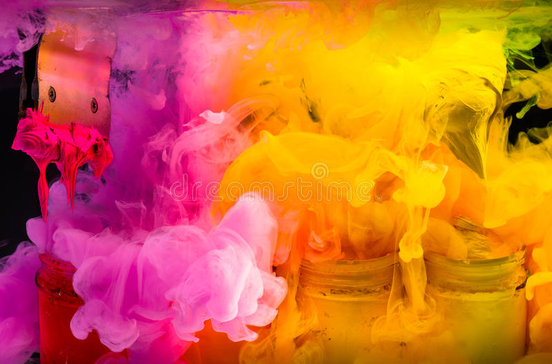 Splash water color ink into the hot tone color of plastisol ink. Place orange color yellow color and red color of plastisol ink on print handle in to the glass stock images
