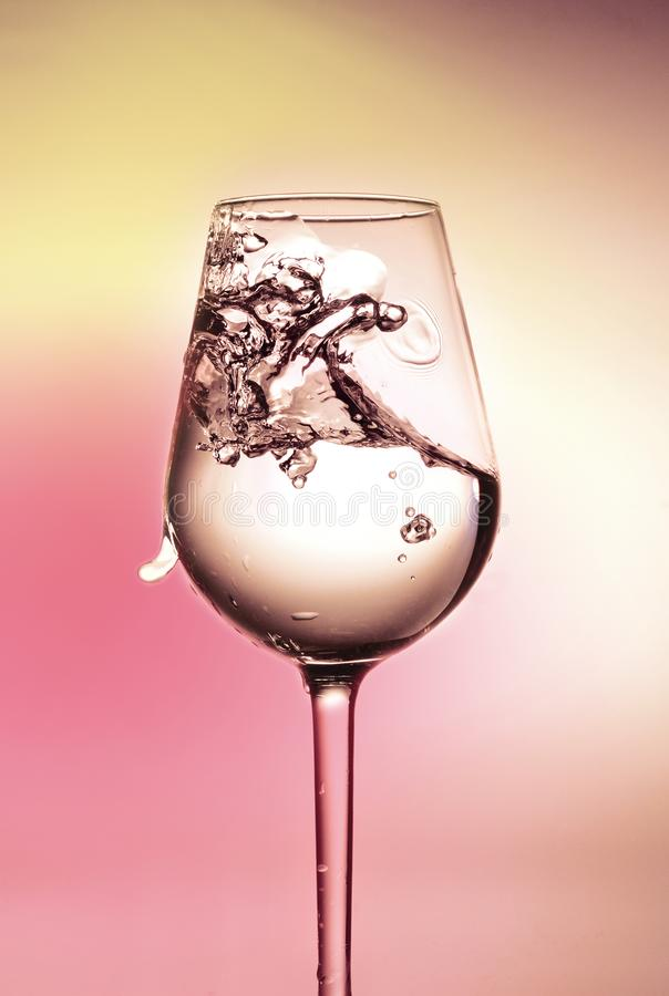 A splash of water in a glass. Beautiful multicolored background. Side view. royalty free stock images
