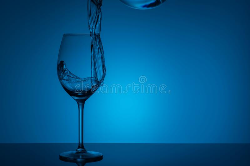 Splash of water in a glass on an blue  background stock photos