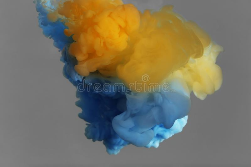 Splash of yellow and light blue  on grey background. Splash of yellow and light blue inks on grey background stock photography
